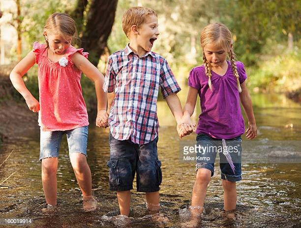 USA, Utah, Lehi, Three kids( 4-5, 6-7) holding hands and walking together in small stream