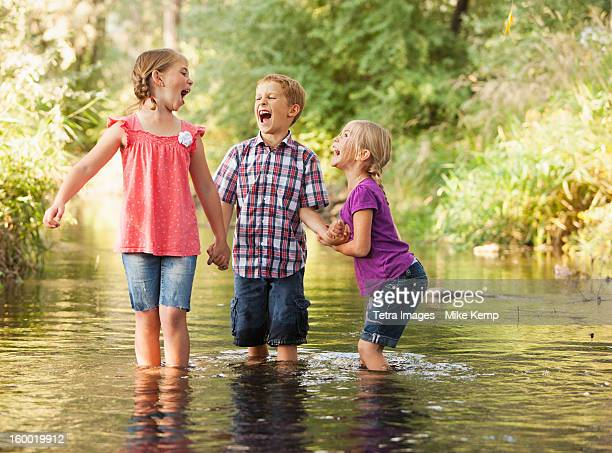 USA, Utah, Lehi, Three kids (4-5, 6-7) playing together in small stream