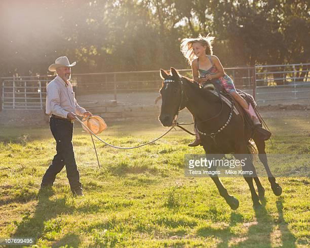 USA, Utah, Lehi, Trainer assisting girl (8-9) riding horse in paddock