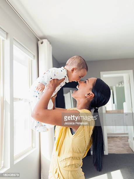 usa, utah, lehi, woman holding up her baby son (3 months) - indian baby stock photos and pictures
