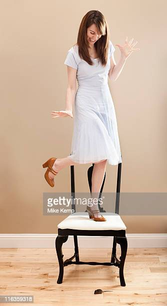USA, Utah, Lehi, Young woman standing on chair, evading mouse