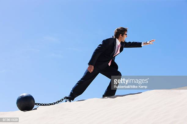 USA, Utah, Little Sahara, businessman wearing ball and chain in desert
