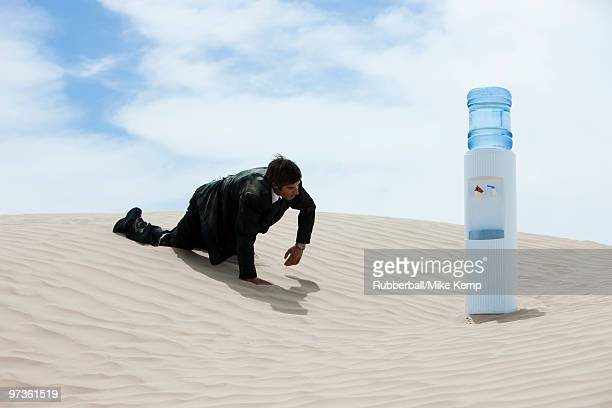 usa, utah, little sahara, mid adult businessman crawling to water cooler on desert - thirsty stock pictures, royalty-free photos & images