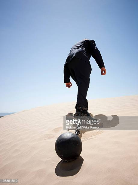 USA, Utah, Little Sahara, mid adult businessman pulling ball in chain on desert, rear view, low angl