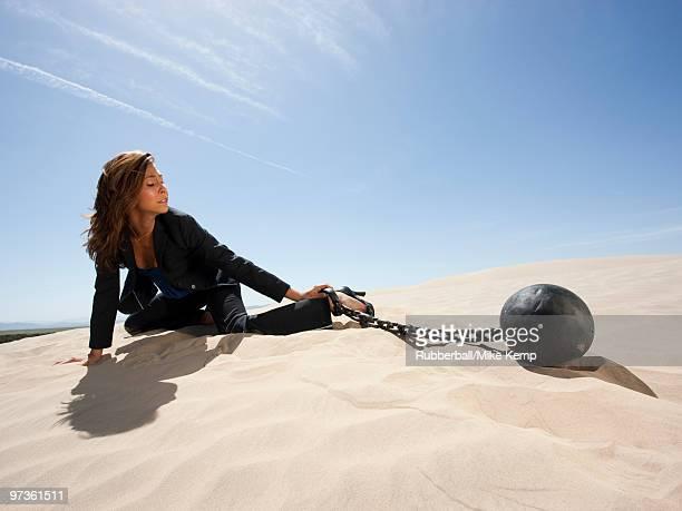 USA, Utah, Little Sahara, young businesswoman pulling ball in chain on desert