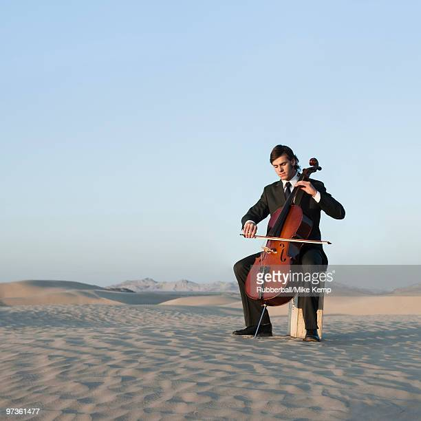 usa, utah, little sahara, young man with cello in desert - cellist stock pictures, royalty-free photos & images