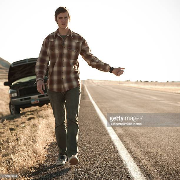 USA, Utah, man hailing on road, broken car in background
