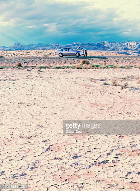 USA, Utah, man looking under bonnet of car in arid landscape
