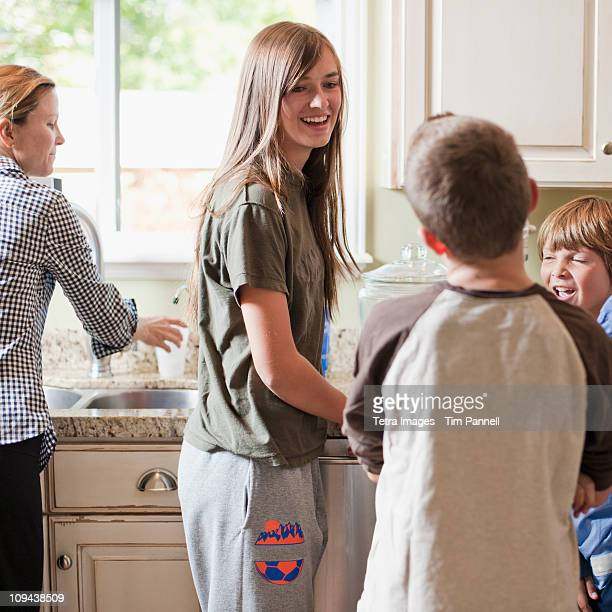 USA, Utah, Mother with three kids (8-9, 10-11, 14-15) in kitchen