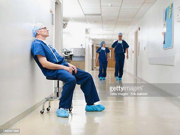 USA, Utah, Ogden, Surgeon resting in hospital corridor after operation, while two of his colleagues are walking in background