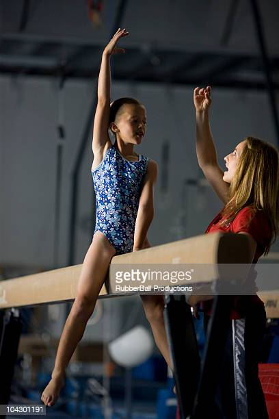 usa, utah, orem, coach training girl gymnast (10-11) on balance beam - girl with legs spread stock photos and pictures