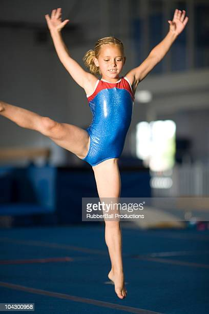 usa, utah, orem, girl (8-9) jumping with legs outstretched in gym - leotard stock photos and pictures