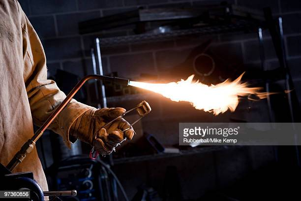 usa, utah, orem, male welder with blowtorch in workshop - in flames i the mask stock pictures, royalty-free photos & images
