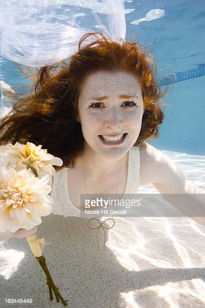 usa, utah, orem, portrait of young bride with bouquet under water - utah wedding stock pictures, royalty-free photos & images