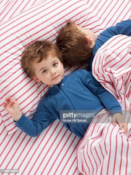 USA, Utah, Orem, Twin boys (2-3) wearing pajamas lying on bed