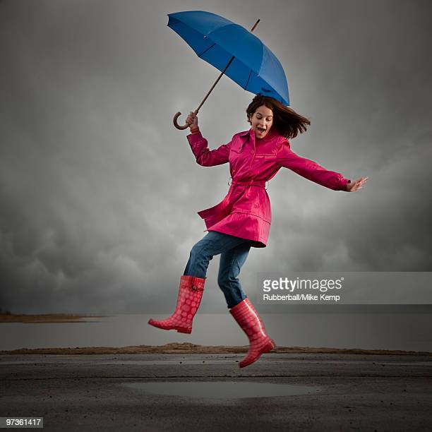 USA, Utah, Orem, woman with umbrella jumping under overcast sky