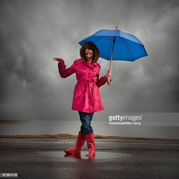 USA, Utah, Orem, woman with umbrella standing in puddle