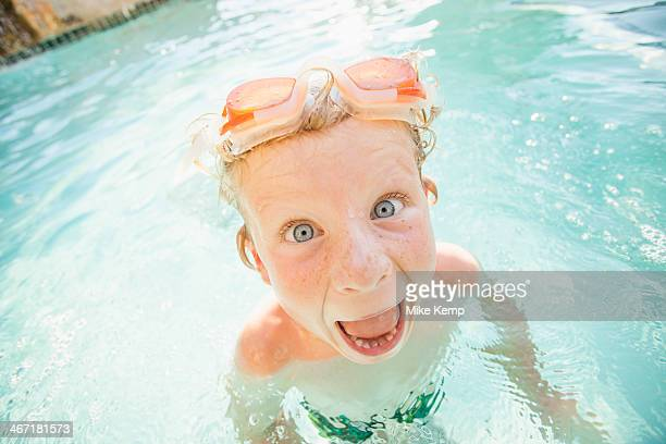 USA, Utah, Park City, Boy (4-5) swimming in swimming pool and making funny face