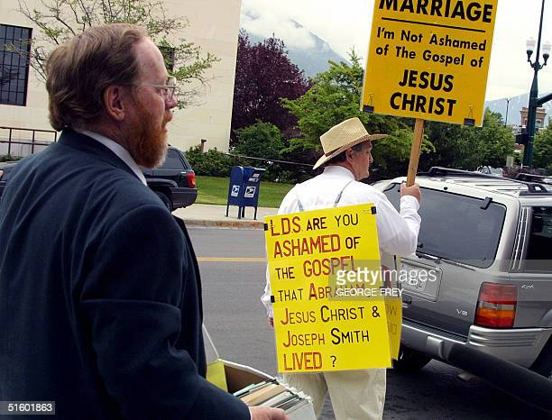 Utah polygamist Tom Green pauses to read the sign of a supporter Gurnie Cook outside 4th District Court in Provo, Utah where the third day of Green's...