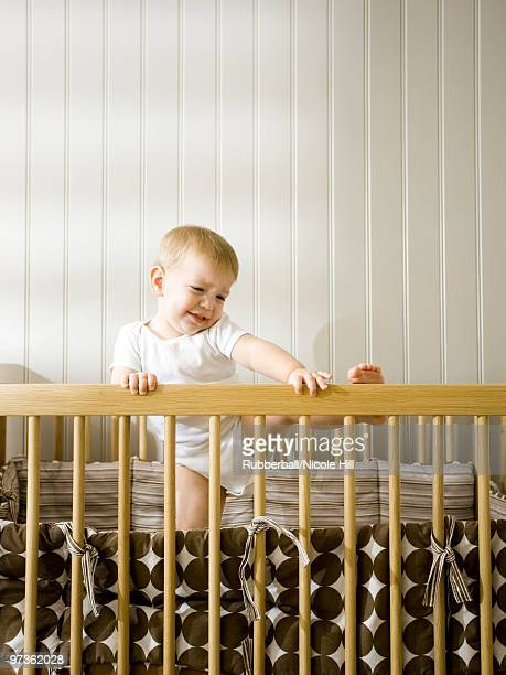 usa, utah, provo, baby boy (18-23 months) climbing in crib - naughty america stock pictures, royalty-free photos & images