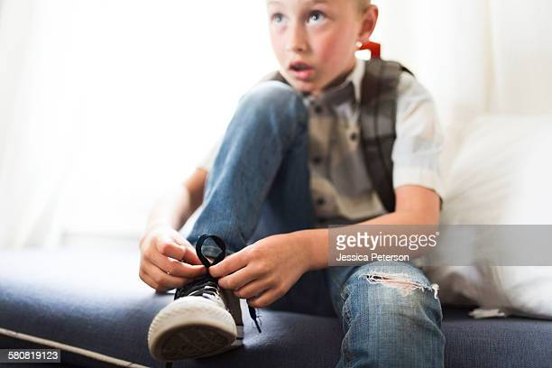 USA, Utah, Provo, Boy (6-7) tying shoes