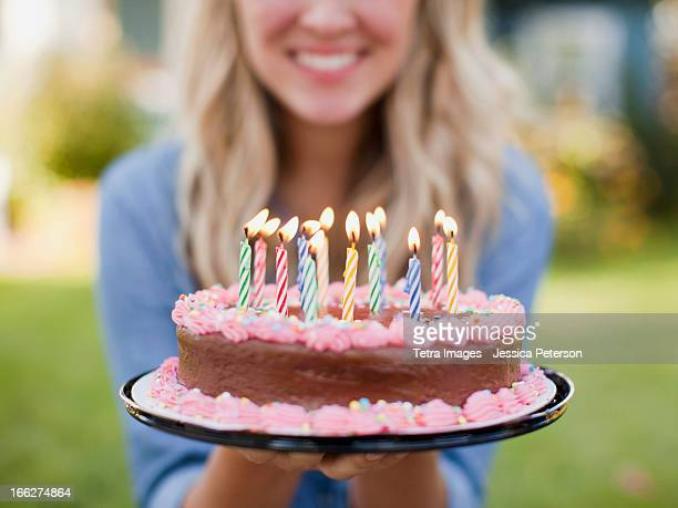 usa, utah, provo, mid-section of young woman holding birthday cake - birthday cake stock photos and pictures