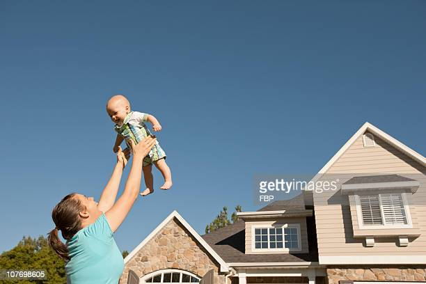 USA, Utah, Provo, Mother lifting baby boy (6-11 months) outside home