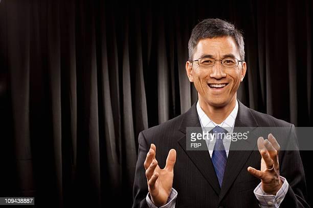 USA, Utah, Provo, Portrait of businessman having speech in front of black curtain
