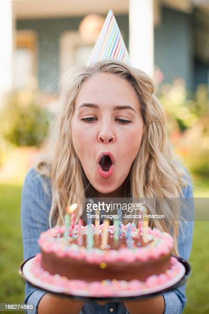 USA, Utah, Provo, Portrait of young woman blowing birthday candles