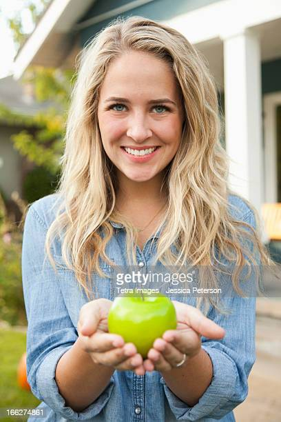 USA, Utah, Provo, Portrait of young woman holding green apple