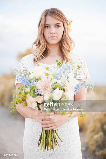 USA, Utah, Provo, Waist-up portrait of bride holding bunch of flowers