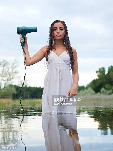 USA, Utah, Provo, woman wading in lake holding hair dryer and hair brush