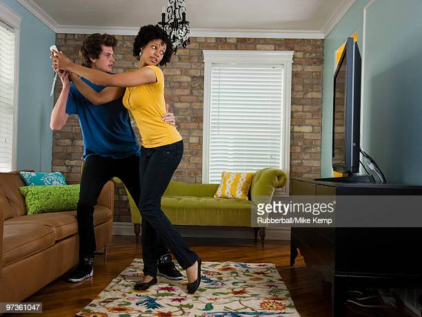 USA, Utah, Provo, young couple holding remote control in living room