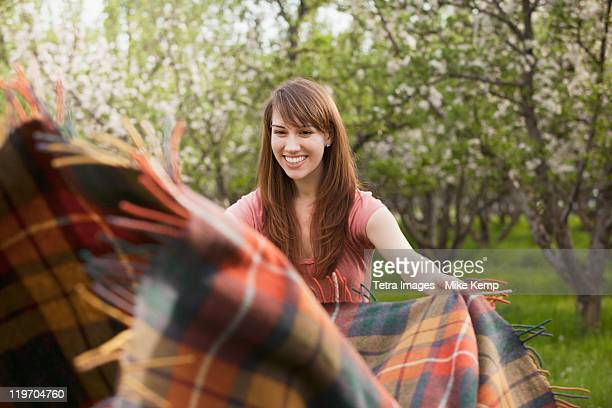 usa, utah, provo, young woman holding blanket in orchard - picnic blanket stock pictures, royalty-free photos & images