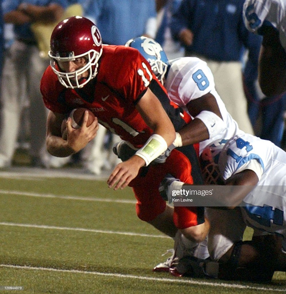 Utah quarterback Alex Smith (11) gets tackled by North Carolina's Tommy Richardson (8) and Gerald Sensabaugh (14) during the first quarter Saturday, Oct. 16, 2004 at Rice-Eccles Stadium in Salt Lake City, Utah