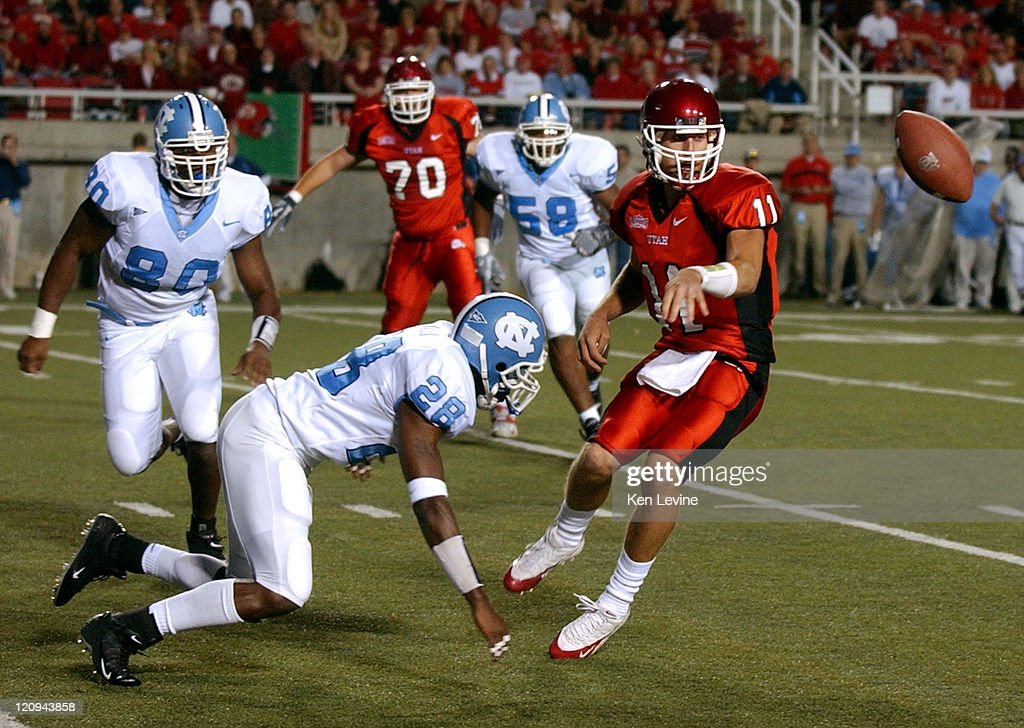 Utah quarterback Alex Smith (11) pitches the ball to his running back Marty Johnson (not shown) who runs it in for a 6 yard touchdown as North Carolina defenders D.J. Walker (28) and Tommy Davis (80) defend during the first quarter Saturday, Oct. 16, 2004 at Rice-Eccles Stadium in Salt Lake City, Utah