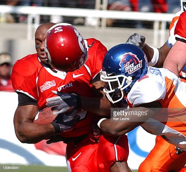 Utah running back Darryl Poston gets his helmet knocked off by the hit of Boise States Gerald Alexander during the third quarter at Rice Eccles...