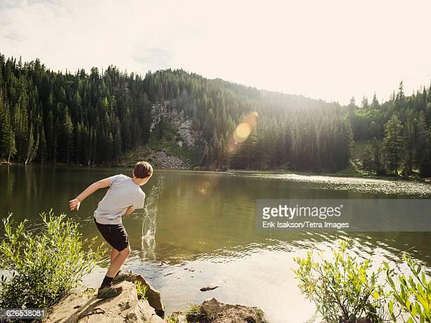 USA, Utah, Salt Lake City, Boy (12-13) throwing stone into lake