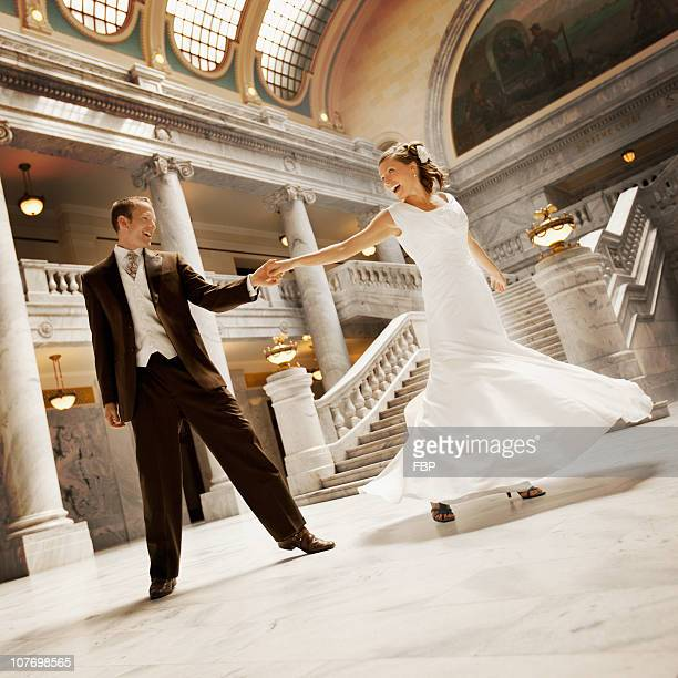 usa, utah, salt lake city, bride and groom holding hands in mansion - utah wedding stock pictures, royalty-free photos & images