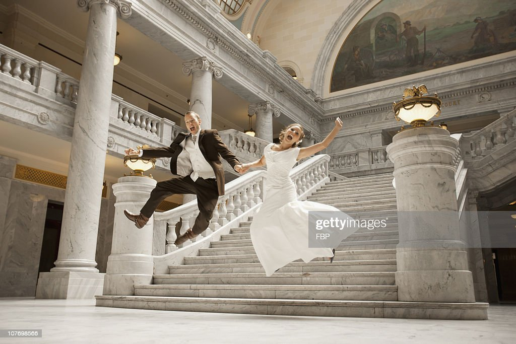 USA, Utah, Salt Lake City, Bride and groom leaping from steps : Stock Photo