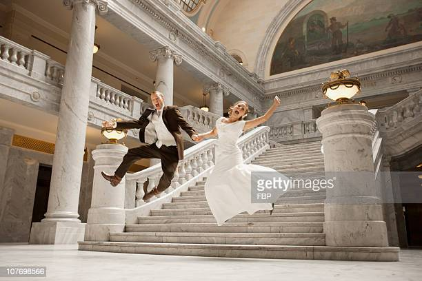 usa, utah, salt lake city, bride and groom leaping from steps - utah wedding stock pictures, royalty-free photos & images