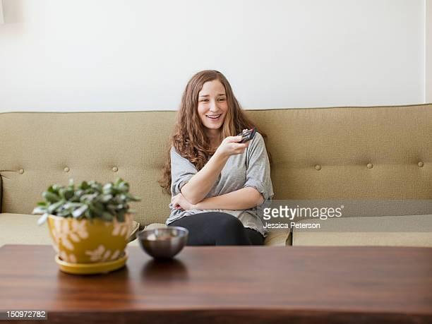 USA, Utah, Salt Lake City, Cheerful young woman sitting on sofa with remote control