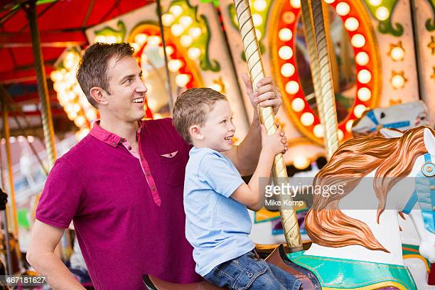 USA, Utah, Salt Lake City, Father and son (4-5) on carousel in amusement park