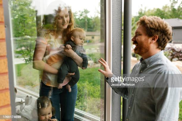 usa, utah, salt lake city, father visiting partner and children (6-11 months, 2-3) through window - 6 11 months stock pictures, royalty-free photos & images