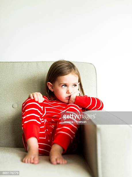 USA, Utah, Salt Lake City, Girl (4-5) in pajamas sitting on sofa