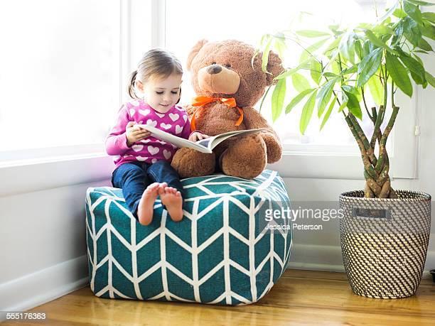 USA, Utah, Salt Lake City, Girl (4-5) sitting with teddy bear on bean bag