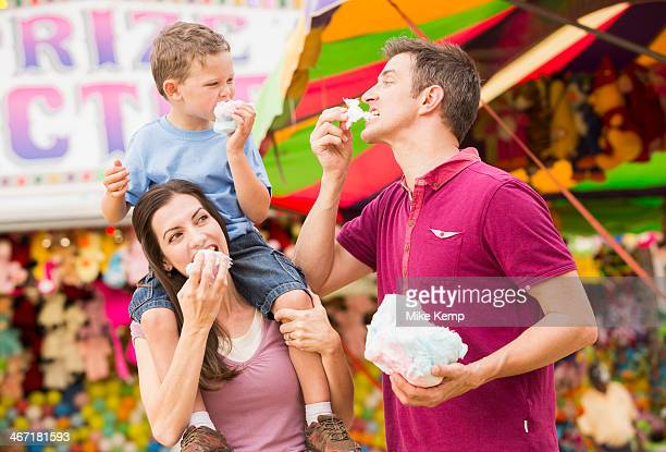 USA, Utah, Salt Lake City, Happy family with son (4-5) in amusement park eating cotton candy