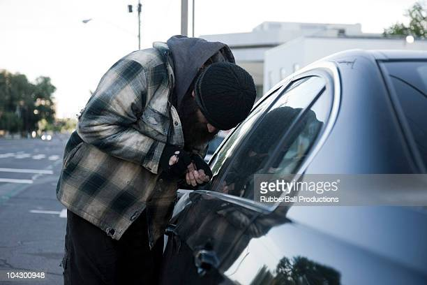 USA, Utah, Salt Lake City, Homeless man breaking into car, side view