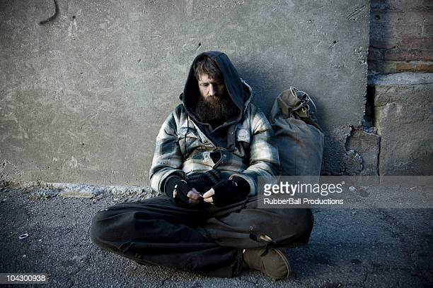 usa, utah, salt lake city, homeless man with sack sitting on sidewalk - homeless stock photos and pictures