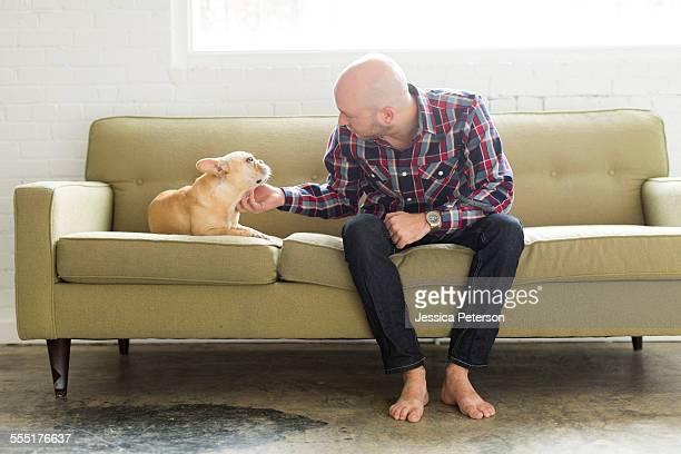 USA, Utah, Salt Lake City, Man sitting on sofa stroking pug